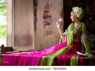 Asian woman wearing Thai traditional dress hand holding lotus flower