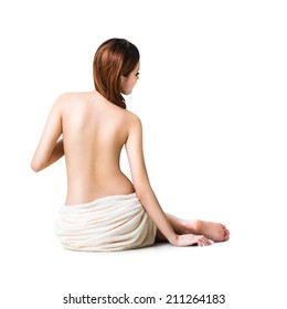 Asian woman wearing towel sitting on the floor back view, Isolated over white