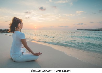 Asian woman wearing white sportswear practicing yoga Lotus pose to meditation on the beach in Maldives at sunset,Feeling so comfortable and relax in holiday,Healthy with Yoga Concept