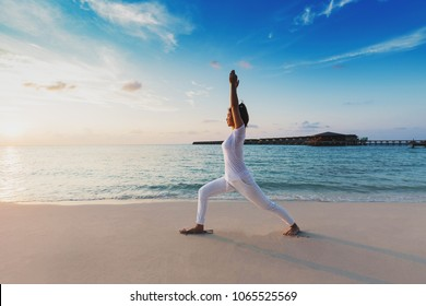 Asian woman wearing white sportswear practicing yoga Warrior one pose stretching exercises muscle for warm up on beach in Maldives at sunset,Feeling so comfortable and relax in holiday,Healthy Concept