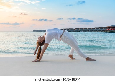 Asian woman wearing white sportswear practicing yoga Camatkarasana pose stretching exercises muscle for warm up on beach in Maldives at sunset,Feeling so comfortable and relax in holiday