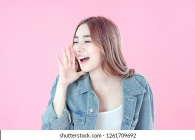 Asian woman whisper about secret to good health, blue jean clothing, pink background