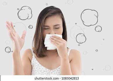 Asian woman in white dress catch her nose because of a bad smell against gray background.