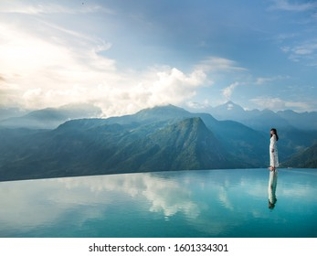 Asian woman in white dress standing on the edge of infinity pool above the Mountain peak in the morning in front of beautiful nature views, Sapa, Vietnam