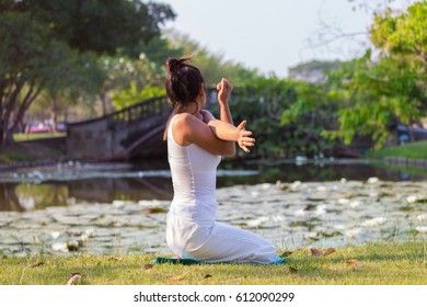 Asian Woman in white Performing yoga in natural Park,morning scene