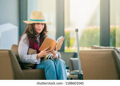 Asian woman in white shirt and hat is reading a book and sitting on a chair in the terminal of the airport terminal.