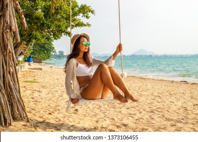 Asian woman in white sitting on a swing  at sand beach and looking beautiful tropical paradise sea . Summer vacation. Summer vibes. Enjoying and relaxing girl on holiday.