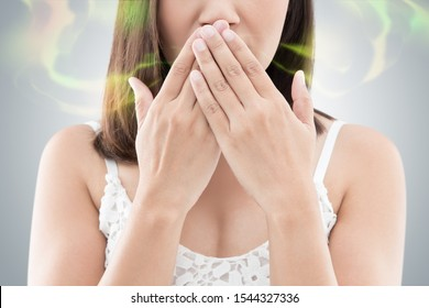 Asian woman in white wear close her mouth against gray background, Bad breath