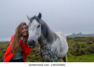 An asian woman with a wild dartmoor pony in the Dartmoor national park, Devon, UK.
