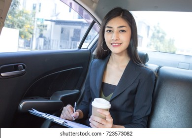 Asian Woman working with attractive smiling in Car, Woman working concept.