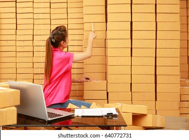 Asian woman working by using pencil counting parcel boxes in her own shopping online business at home with laptop computer on desk