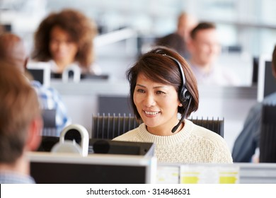 Asian woman working in call centre, surrounded by colleagues