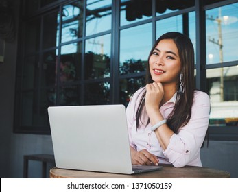 Asian woman working in coffee shop with laptop.
