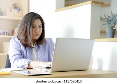 The Asian woman working in the home studio.