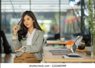 Asian woman working with laptop in coffee shop cafe,she thinking and holding pen