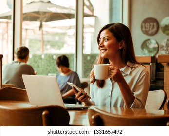 Asian woman working with laptop in coffee shop cafe