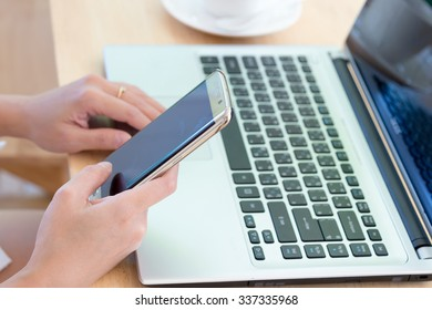 Asian woman working with laptop and coffee, holding mobile phone