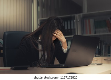 Asian woman working in office,young business woman stressed from work overload with a lot file on the desk,Thailand people thinking something