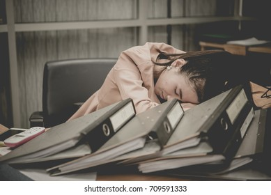 Asian woman working in office,young business woman stressed from work overload with a lot file on the desk