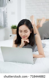 Asian woman working on bed.