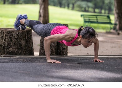 Asian woman working out by doing leg raise decline push up in the park