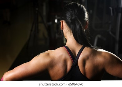Asian woman working out in gym from behind