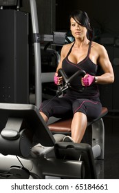 Asian woman working out on rower in gym