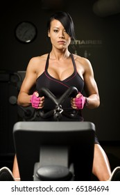 Asian woman working out on rower inside gym