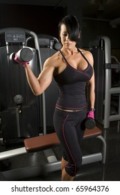 Asian woman working out with weights in gym