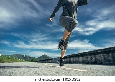 Asian woman is workout and running at the morning, she is warm up her body and drinking water.She listening the music from her smart-phone. Healty and sport lifestyle concept.
