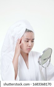 Asian woman worrying about her skin look into the mirror. concern the problems. Beauty concept of Skin care. on white background