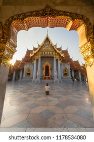 Asian woman worships Bhudda statue at Bangkok's Marble Temple, Wat Benchamabophit Dusitvanaram, Bangkok, Thailand