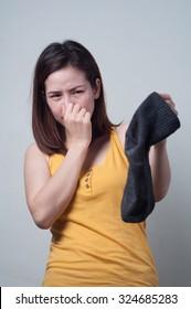Asian woman in a yellow dress smelling socks foul.