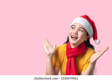 Asian woman in yellow dress wearing red scarf and Santa hat, holidays concept