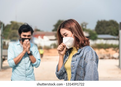 Asian woman yellow t-shirt wearing the N95 Respiratory Protection Mask against air pollution at road and traffic