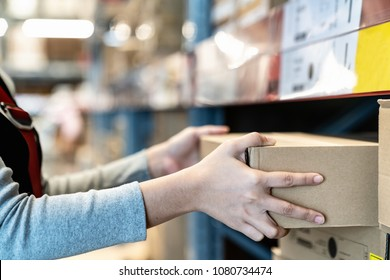 Asian woman's hand shopping in self picking box,package and collect product from shelf,rack in warehouse,store.Worker shipping and delivery packaging business concept with copy space.Courier shipment.