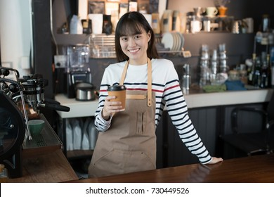 Asian womanstanding smiling with a cup of coffee in her hand