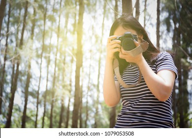 Asian women age between 25-30 years old hold the digital camera up to take a photo.