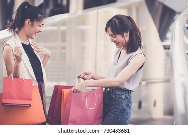 Asian women are amazed during shopping and holding shopping bags, female with the joy of shopping ,online shopping,social media concept.