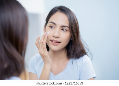 Asian women applying face lotion.