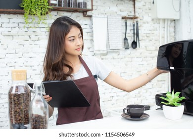 Asian Women Barista checking to coffee machine at couter. Barista female working at cafe. Working woman small business owner or sme concept. Vintage tone.
