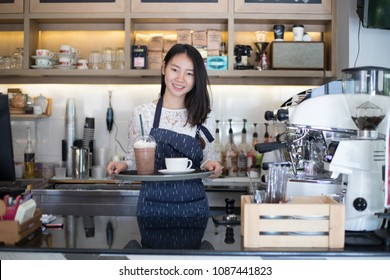 Asian women Barista smiling  in coffee shop counter.business owner food and drink cafe concept