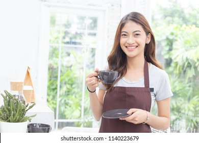 Asian Women Barista smiling and looking to camera in coffee shop counter. Barista female holding coffee cup at cafe. Working woman small business owner or sme concept.