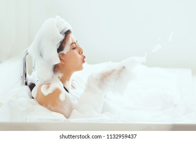 Asian women are bathed in bathtubs in their homes and in bathtubs filled with soap bubbles. The girl is enjoying her bath and feels comfortable and relaxed.