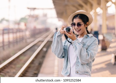 Asian women be smile with camera Travel Holiday Relaxation Concept at train station in Thailand , Vintage Style.