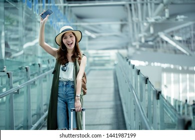 Asian women, beautiful young travelers walking to greet friends Or waving say hello with friends at airport.