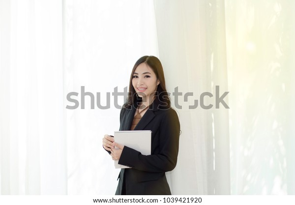 Asian women In black suit Standing holding a white book and smiling happily at work in the morning.