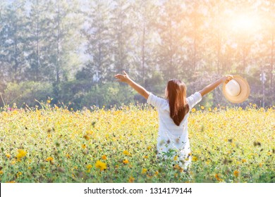Asian women with blooming flower in the garden. Fresh spring and summer floral meadow.