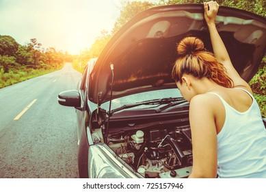 Asian women the car is broken road. Open the bonnet, check engine