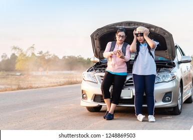 Asian women the car is repair inside road. Open the bonnet call phone on hand,assistance